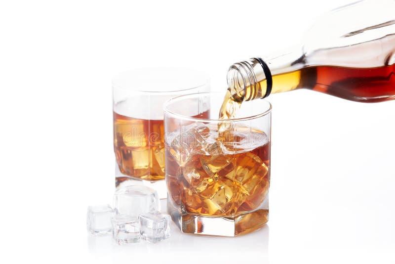 Bottiglia di whiskey e di due vetri versarsi immagine stock libera da diritti