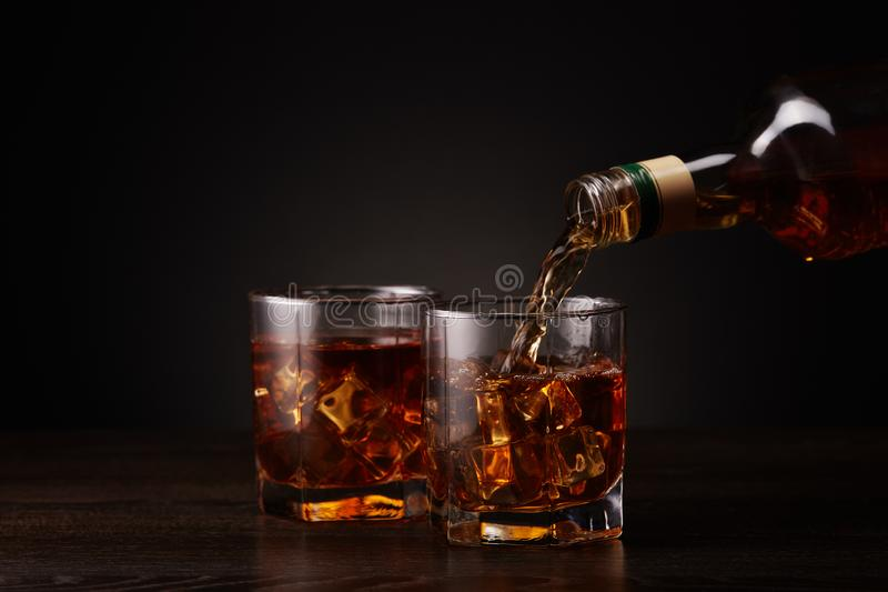 Bottiglia di whiskey e di due vetri versarsi immagini stock