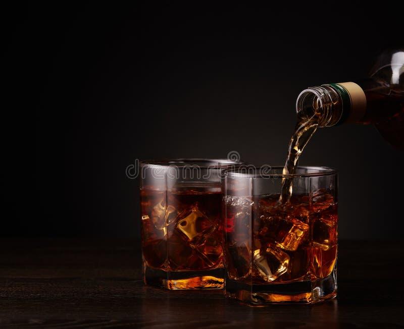 Bottiglia di whiskey e di due vetri versarsi immagine stock