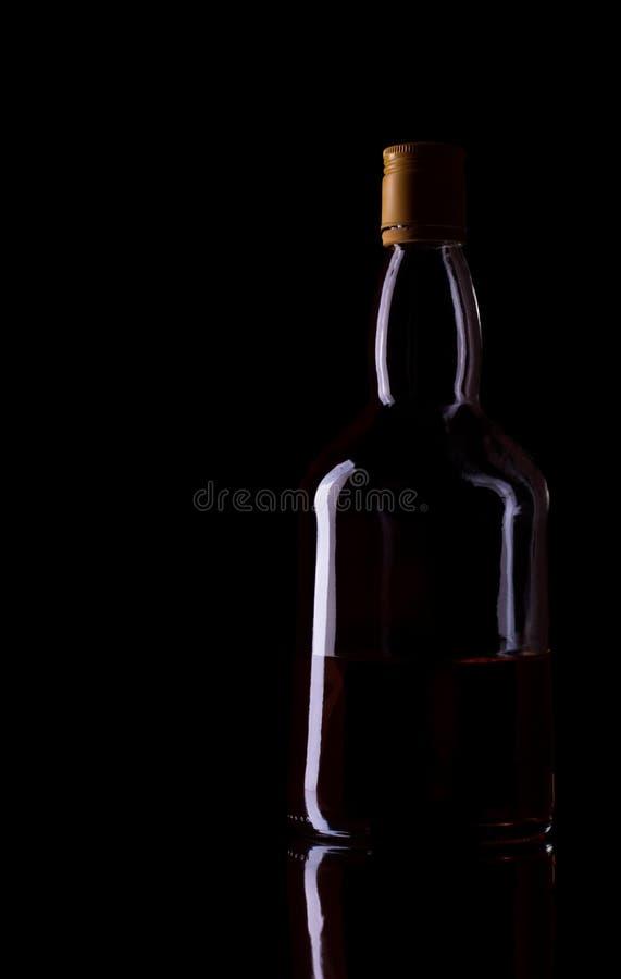 Bottiglia di whisky sul nero fotografia stock