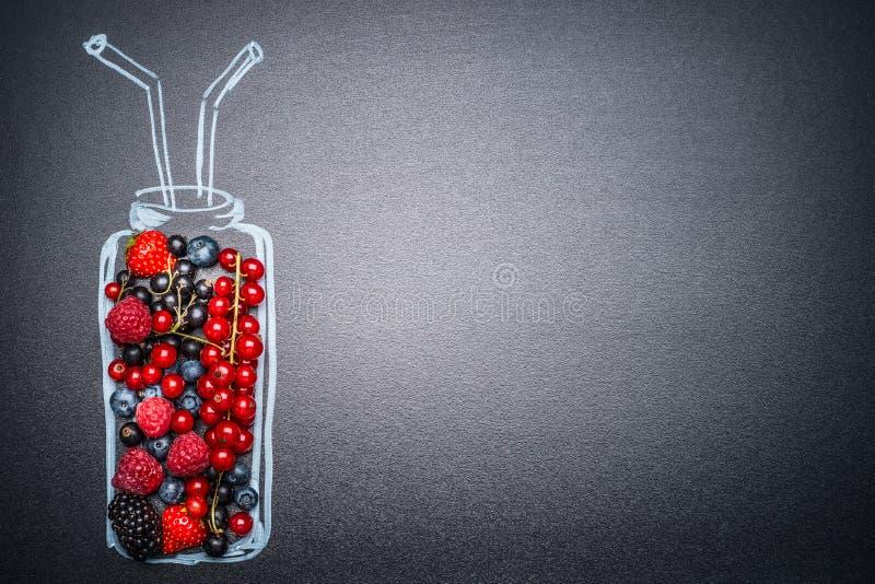 Bottiglia dipinta con le varie bacche fresche per il frullato o il succo che fa sul fondo scuro della lavagna fotografia stock libera da diritti