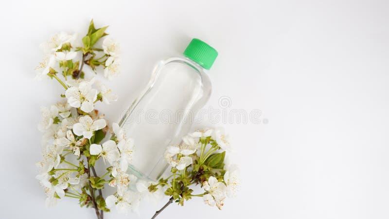Bottiglia disposta per derisione su su fondo e sui fiori bianchi Il concetto dei prodotti di bellezza naturali immagine stock