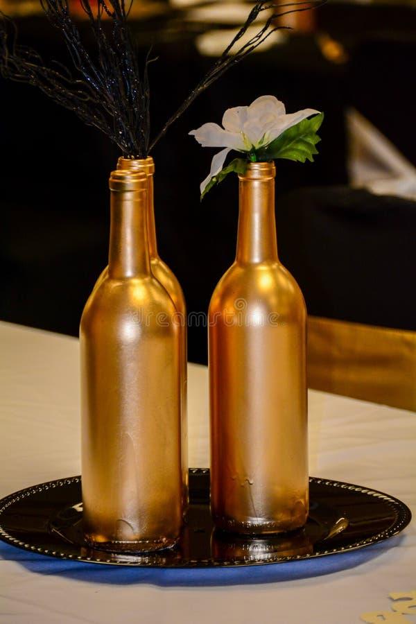 Bottiglia dorata due con il fiore immagine stock libera da diritti