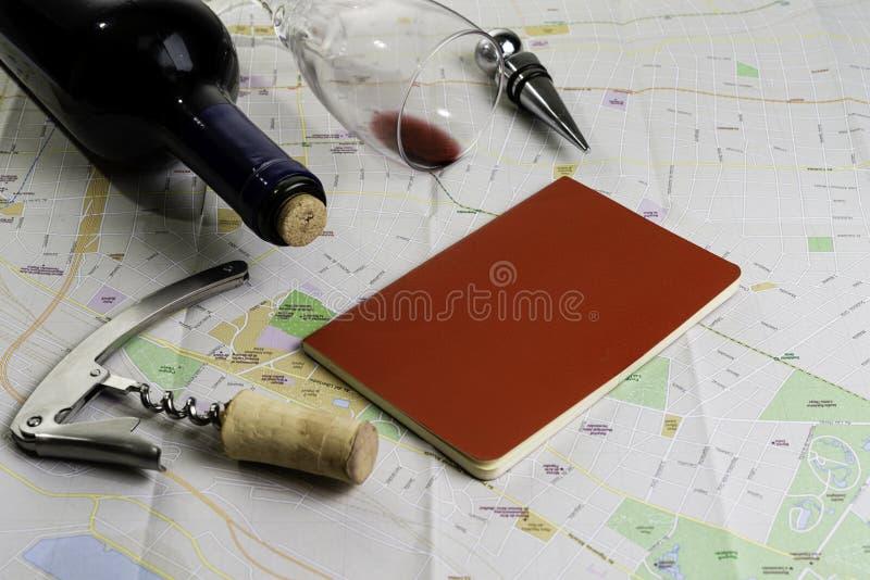 Bottiglia e bicchiere di vino e sugheri sulla mappa per pianificazione dell'itinerario Taccuino rosso per le note fotografia stock libera da diritti