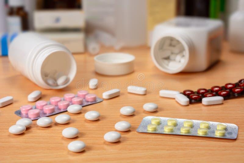 Bottiglia e pillole sparse sulla tavola immagini stock libere da diritti