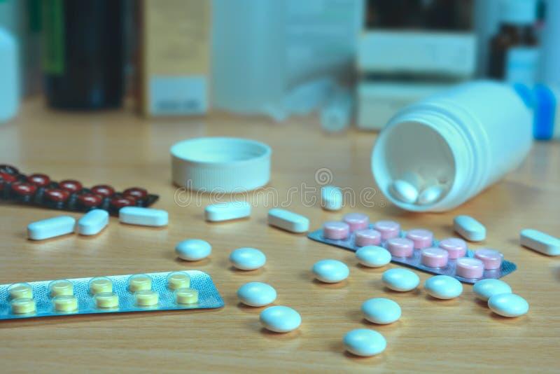 Bottiglia e pillole sparse sulla tavola fotografie stock