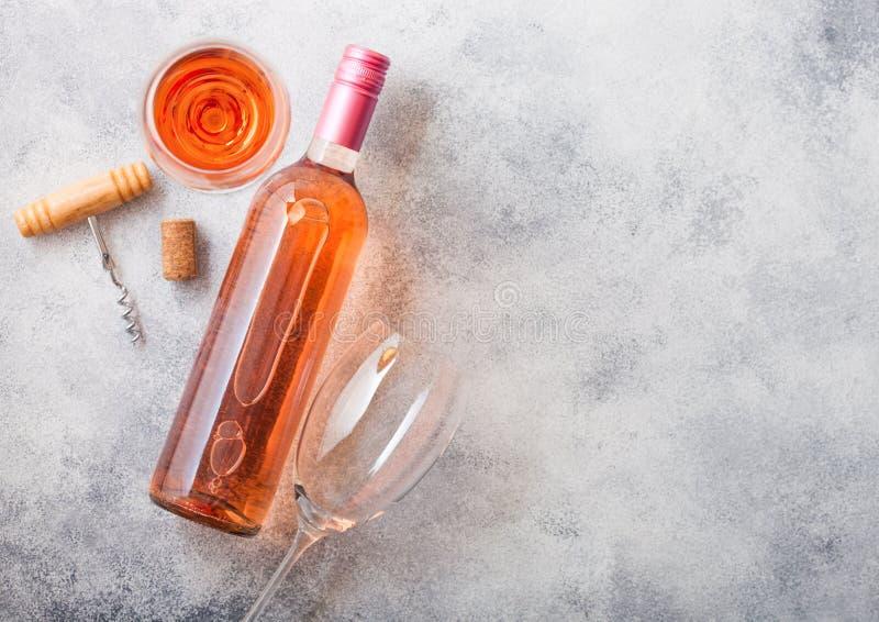 Bottiglia e vetri di vino rosato rosa con l'apri della cavaturaccioli e del sughero sul fondo di pietra del tavolo da cucina Vist immagine stock libera da diritti