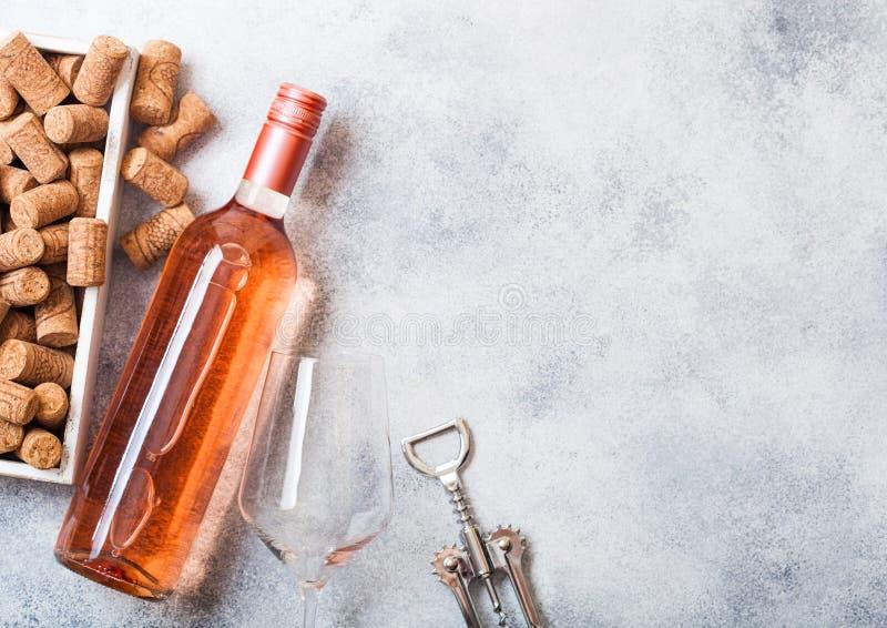 Bottiglia e vetri di vino rosato rosa con la scatola dei sugheri e l'apri della cavaturaccioli sul fondo di pietra del tavolo da  immagine stock