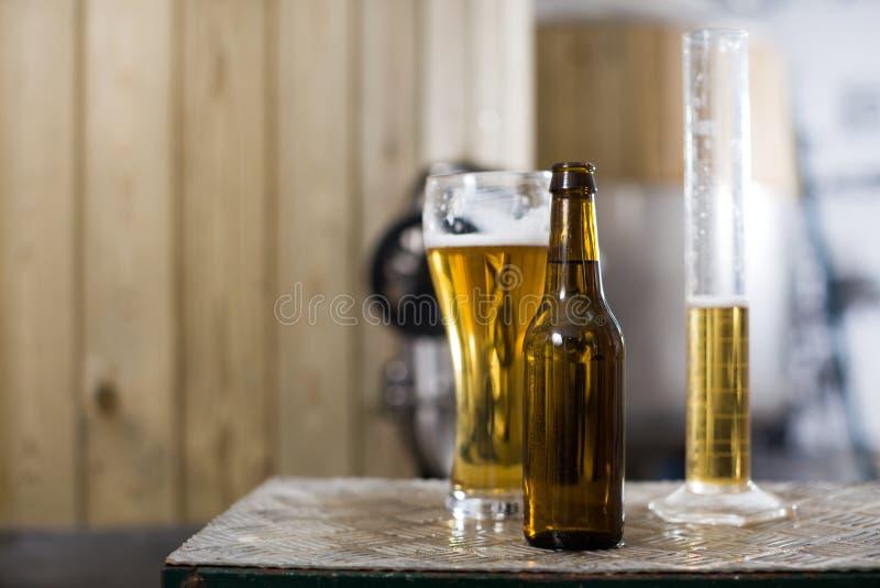 Bottiglia e vetro con la birra dell'oro sui precedenti dei barilotti per fermentazione fotografia stock libera da diritti