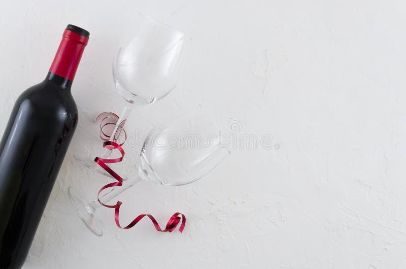 Bottiglia e vetro del vino rosso che si trovano sul fondo bianco Vista superiore con spazio per il vostro testo fotografia stock