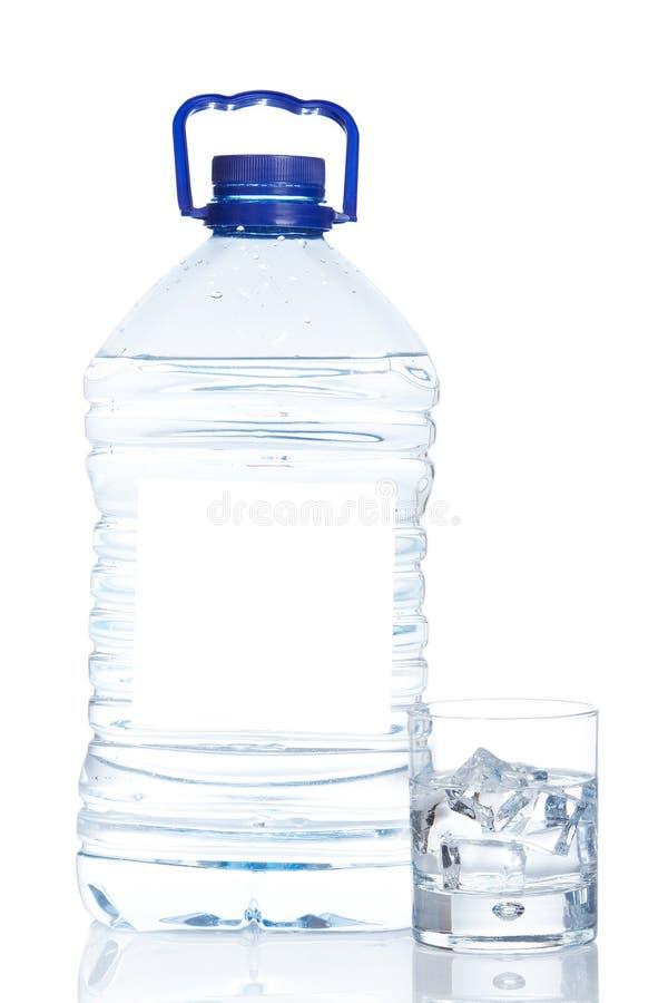 Bottiglia e vetro di acqua minerale con le goccioline immagini stock libere da diritti