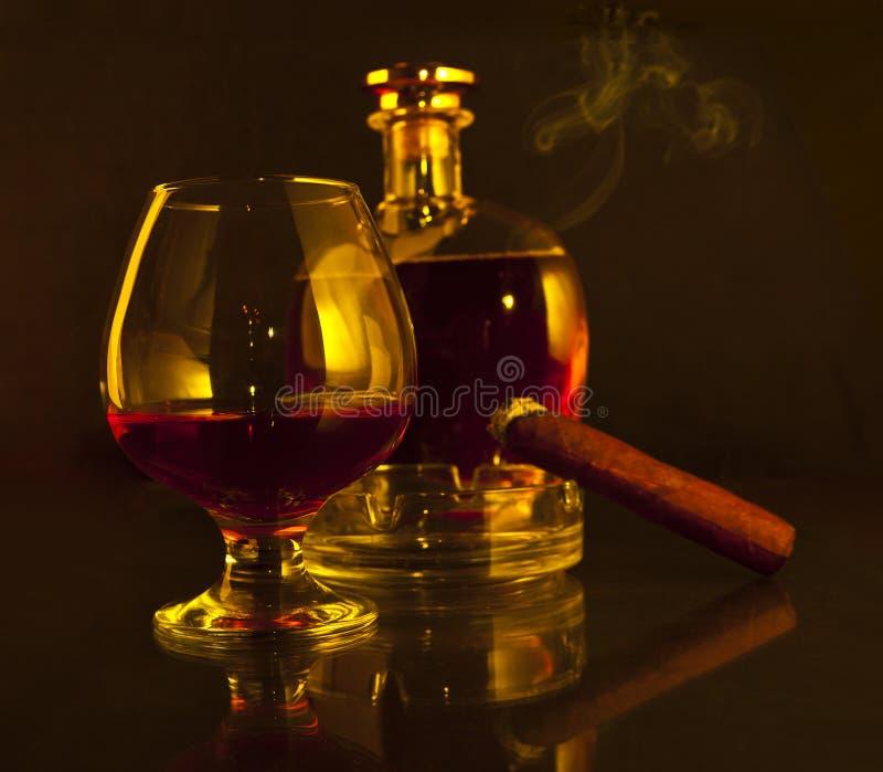 Bottiglia e vetro di brandy e del sigaro immagini stock