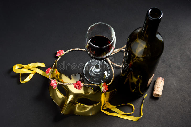 Bottiglia e vetro di vino con la maschera fotografie stock