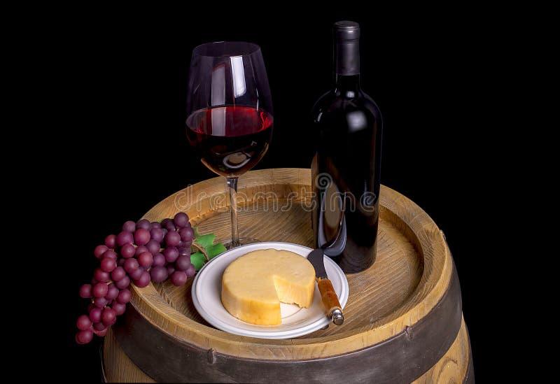Bottiglia e vetro di vino rosso con l'uva ed il formaggio sul barilotto fotografia stock