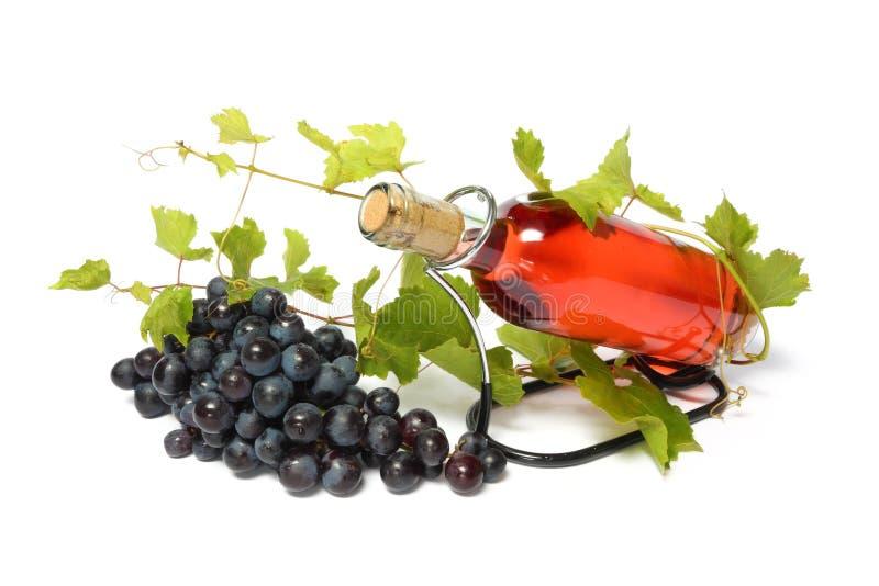 Bottiglia ed uva di vino della Rosa fotografie stock libere da diritti