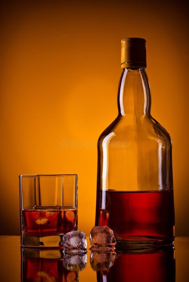 Bottiglia, ghiaccio e vetro di whisky fotografie stock libere da diritti