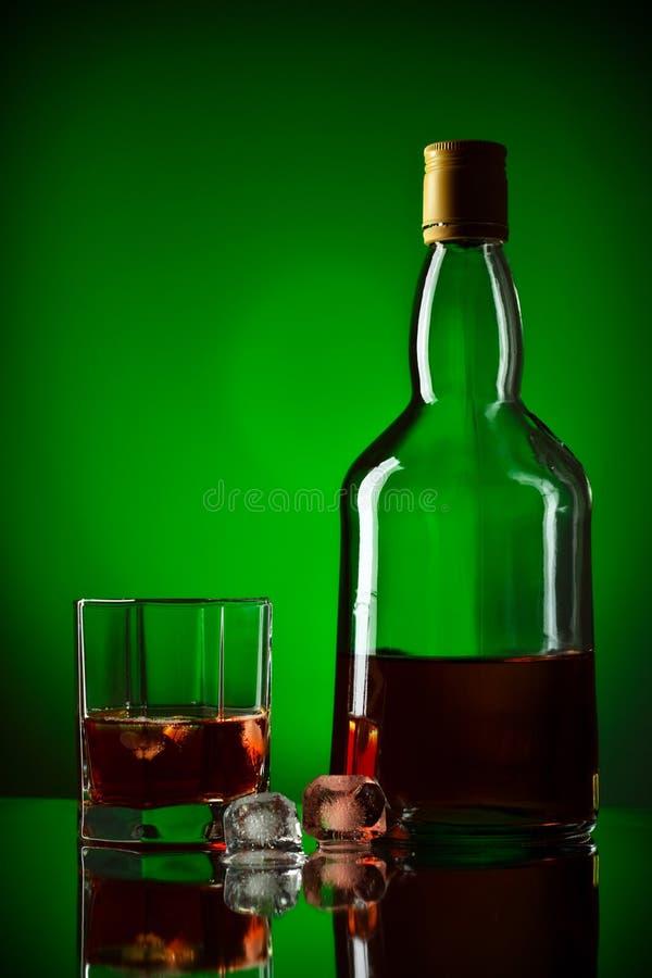 Bottiglia, ghiaccio e vetro di whisky immagini stock