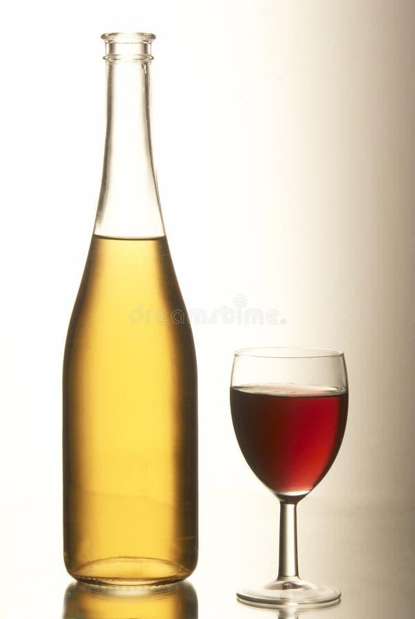 Bottiglia gialla con una coppa piena di vino rosso. fotografia stock