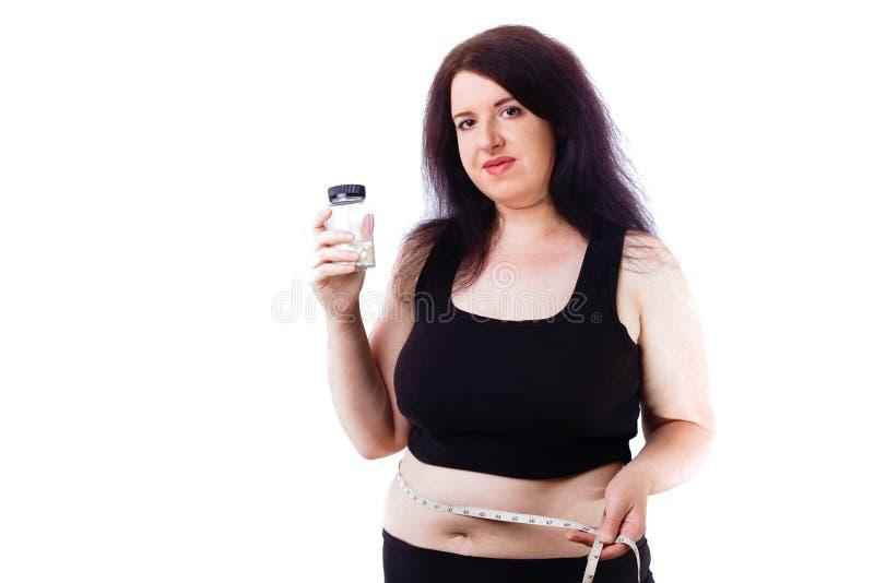 Bottiglia grassa di peso eccessivo di manifestazione della donna con le pillole esili e la t di misurazione immagine stock