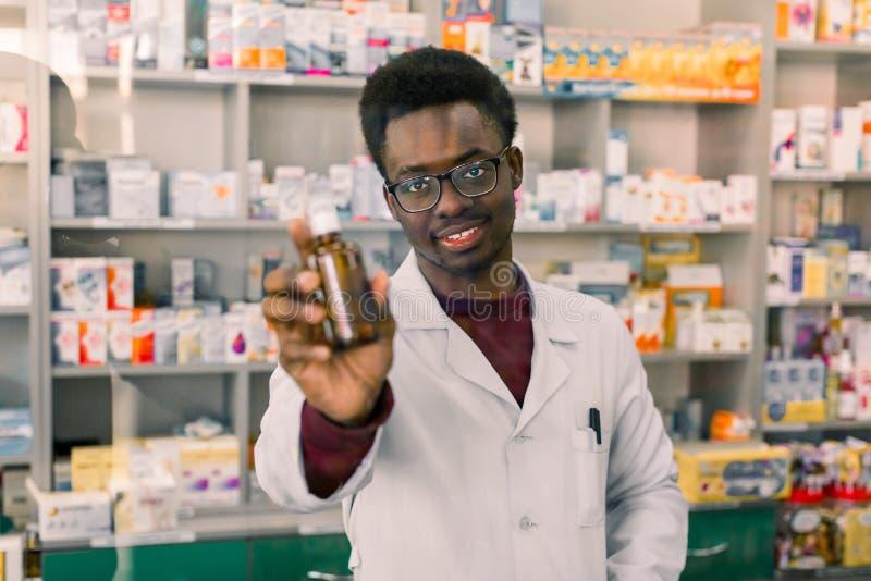 Bottiglia maschio afroamericana professionale di rappresentazione del farmacista di medicina secondo la prescrizione del cliente  fotografia stock libera da diritti