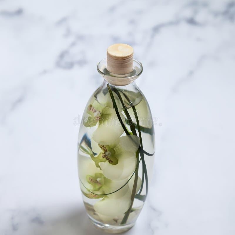 Bottiglia naturale dell'essenza dell'olio del profumo con i petali del fiore dell'orchidea Isolato fotografie stock libere da diritti