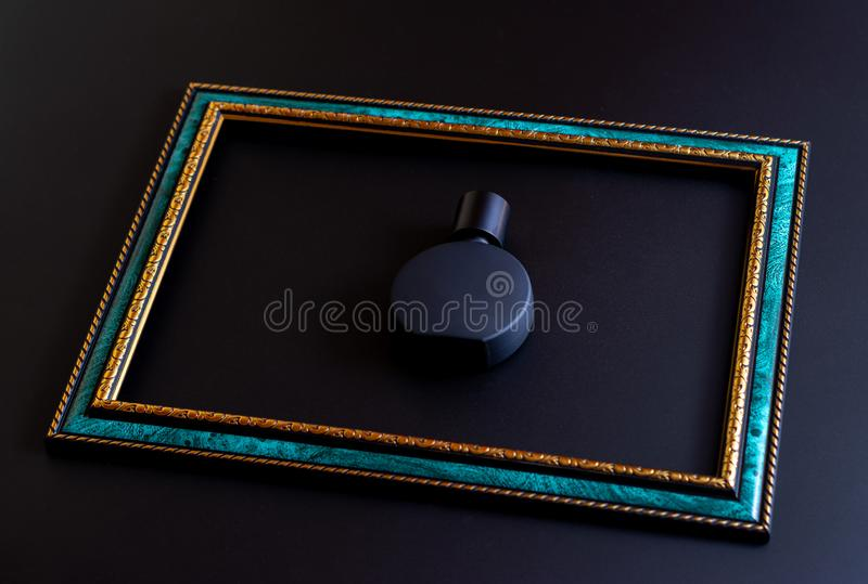 Bottiglia opaca nera per il primo piano unisex del profumo dentro la struttura verde smeraldo con oro rasentare un fondo scuro, f fotografie stock libere da diritti