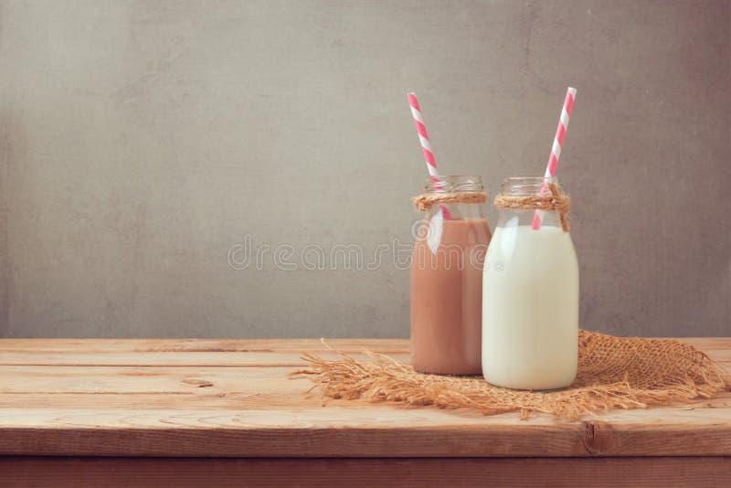 Bottiglia per il latte e bottiglia del latte al cioccolato sulla tavola di legno Cibo sano immagine stock libera da diritti