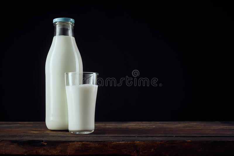 Bottiglia piena di latte accanto alla tazza con lo spazio della copia immagine stock