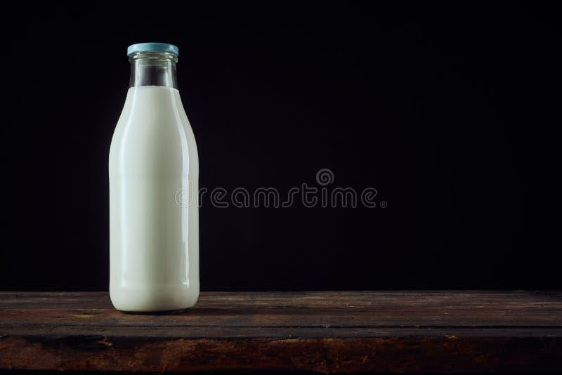 Bottiglia piena di latte accanto alla tazza con lo spazio della copia fotografie stock