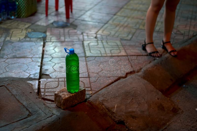Bottiglia in pieno di benzina da vendere su un marciapiede fotografia stock