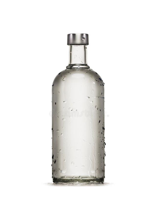 Bottiglia pulita trasparente bagnata dell'alcool con le gocce isolata su fondo bianco fotografia stock