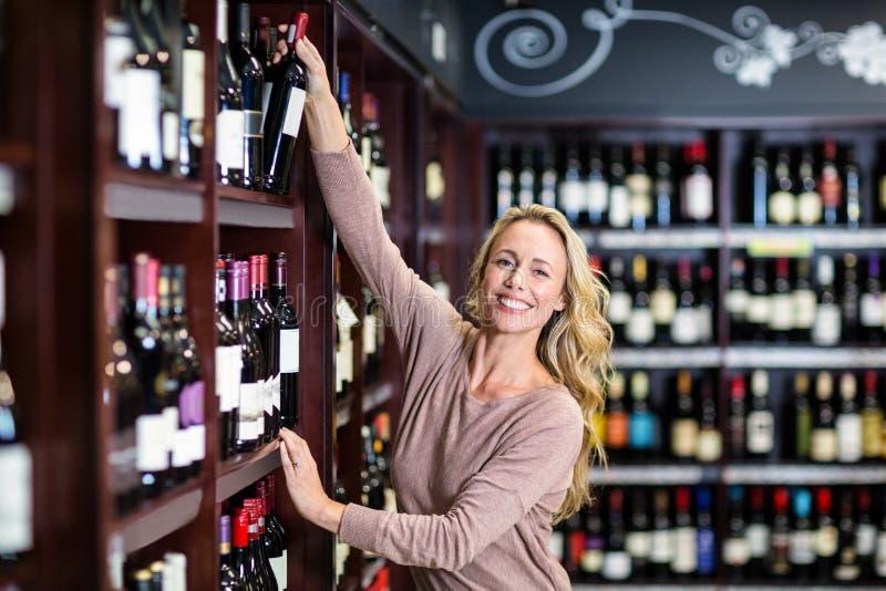 Bottiglia sorridente di raccolto della donna di vino immagini stock libere da diritti