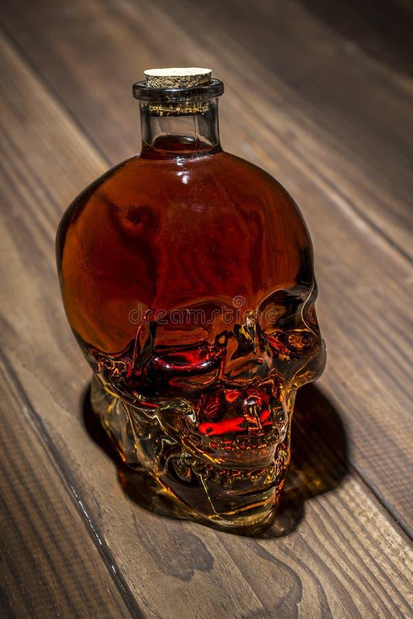 Bottiglia sotto forma di un cranio con alcool Il concetto di danno da alcool alcolismo immagini stock