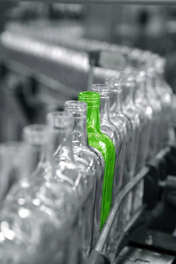 Bottiglia verde unica differente nella riga della fabbrica fotografie stock libere da diritti