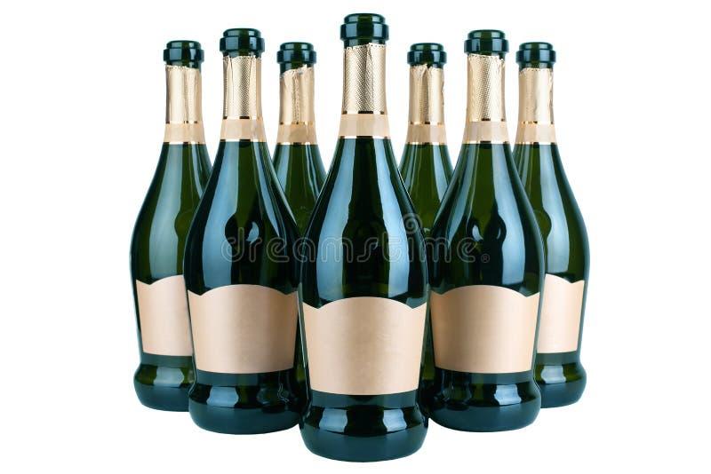 Bottiglie aperte di champagne o di vino spumante con l'etichetta dorata in parecchie file su fondo bianco isolato vicino su, disp immagine stock