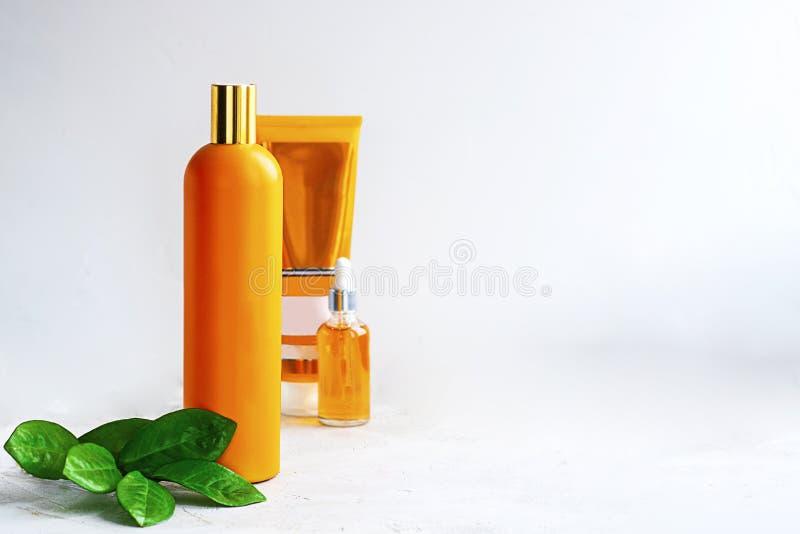 Bottiglie arancio, una a fuoco e foglie verdi del modello accanto loro su fondo bianco Esponga al sole i cosmetici di effetto di  fotografie stock