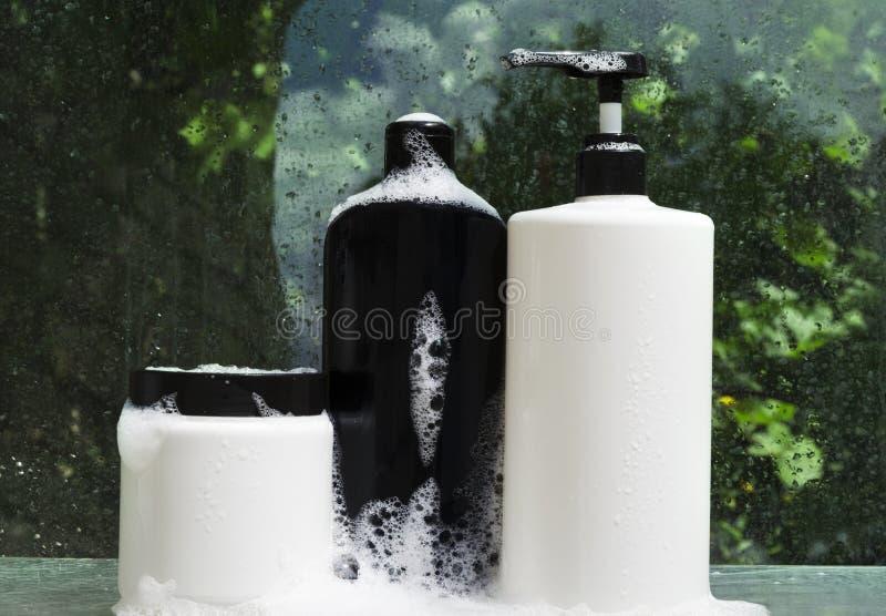 Bottiglie in bianco dei prodotti di bellezza, schiuma su che sta sullo scaffale di vetro bagnato contro le piante verdi immagine stock libera da diritti