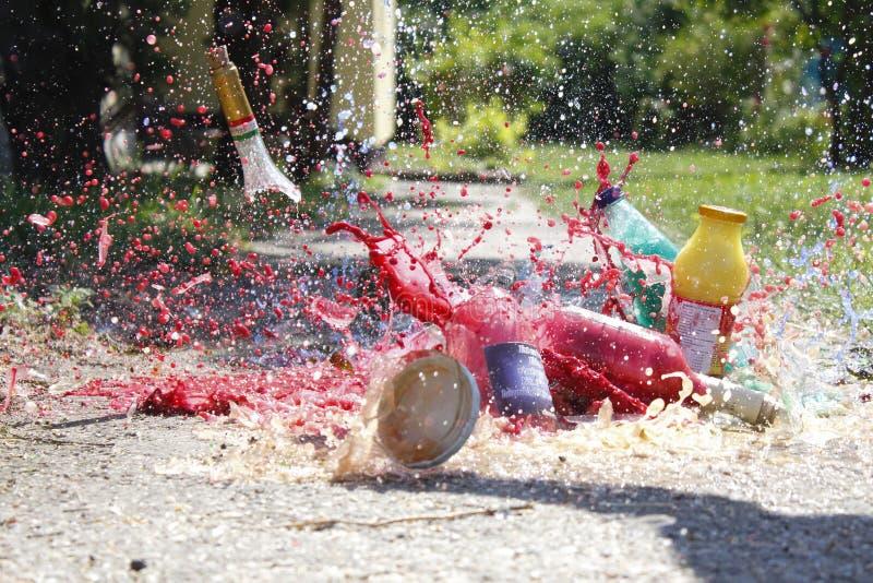 Bottiglie che cadono e che si schiantano riempite di pittura fotografia stock