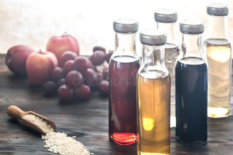 Bottiglie con differenti generi di aceto immagine stock