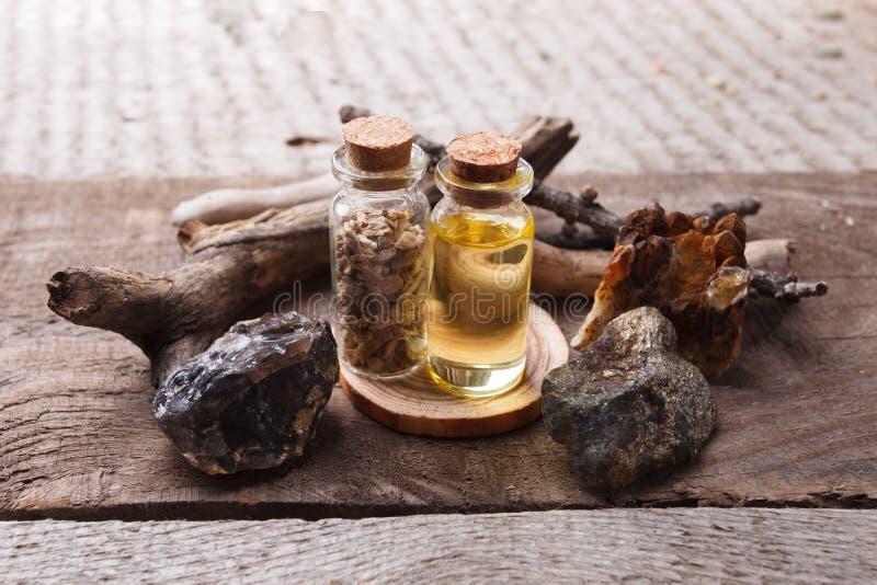 Bottiglie con emulsione, le pietre ed i dettagli di legno Concetto occulto, esoterico, di divinazione e di wicca Farmacista misti immagini stock