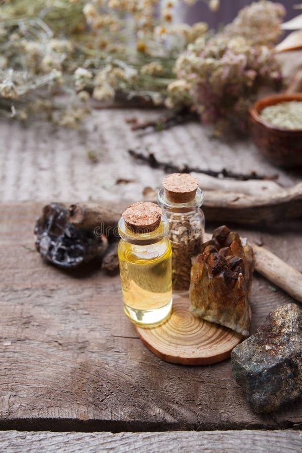 Bottiglie con emulsione, le pietre ed i dettagli di legno Concetto occulto, esoterico, di divinazione e di wicca Farmacista misti fotografia stock libera da diritti