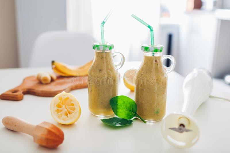 Bottiglie con il frullato della banana e degli spinaci con gli ingredienti Dieta sana della disintossicazione fotografie stock