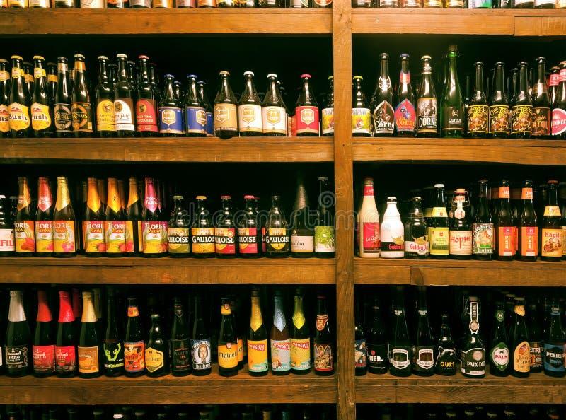 Bottiglie con la birra del Belgio del mestiere, le specie differenti e molte fabbriche di birra nella barra locale per i bevitori immagini stock libere da diritti