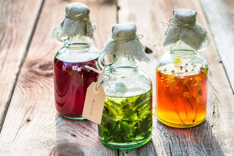 Bottiglie con miele, il tiglio, la menta e l'alcool come medicina naturale fotografia stock libera da diritti