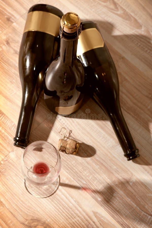 Bottiglie con vino ed il vetro di vino vuoto fotografie stock libere da diritti