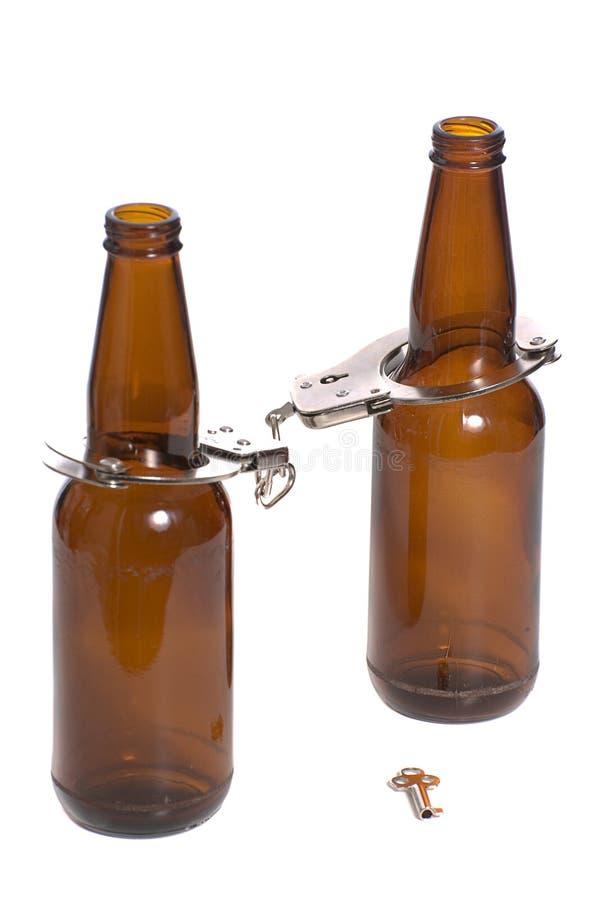 Bottiglie da birra con le manette fotografie stock