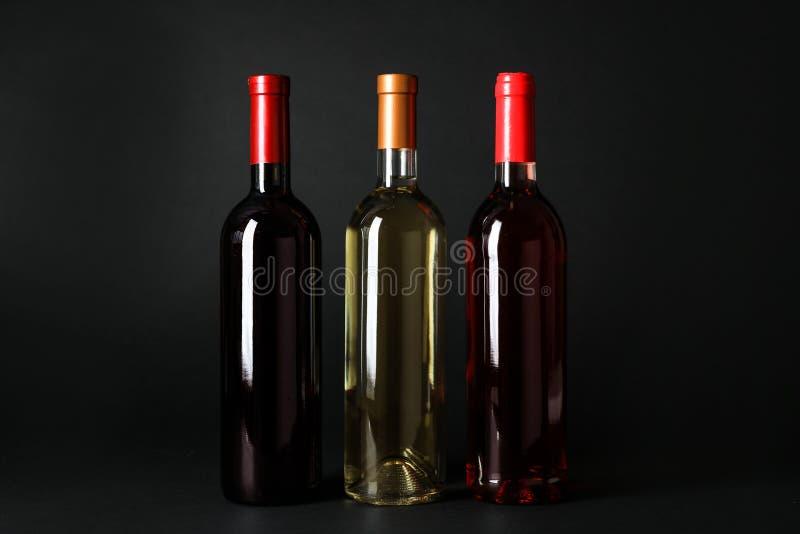 Bottiglie dei vini su fondo scuro fotografia stock