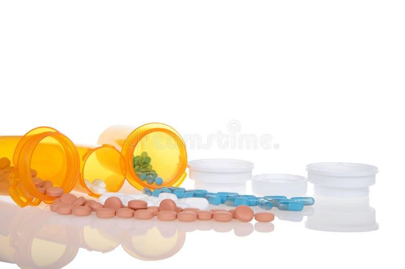 Bottiglie del farmaco rovesciate su superficie riflettente immagini stock