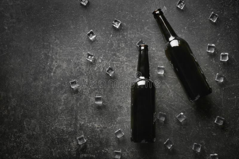 Bottiglie di birra con i cubetti di ghiaccio su fondo scuro immagine stock