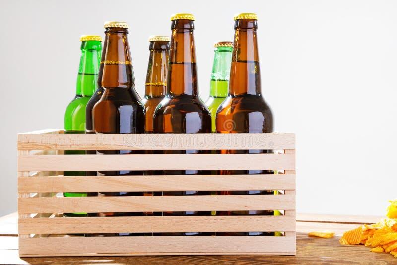 Bottiglie di birra in scatola di legno Chip dorati ondulati Vista superiore Fuoco selettivo Derisione su Copi lo spazio mascherin immagine stock